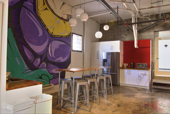 The inside of an office that is very casual with a purple and yellow mural on the wall