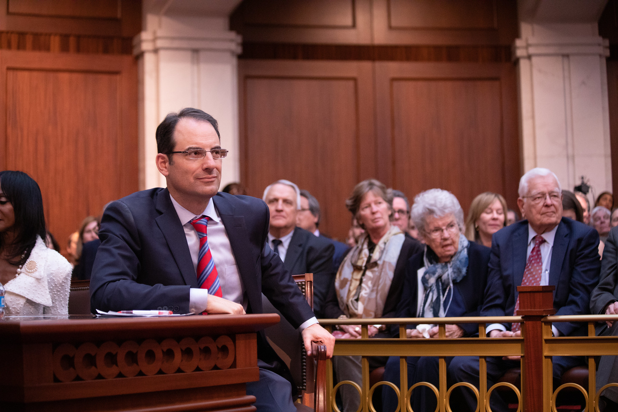 Attorney General Phil Weiser sitting at a table in a court room