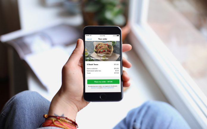 A cell phone shows the order screen on the Grubhub app
