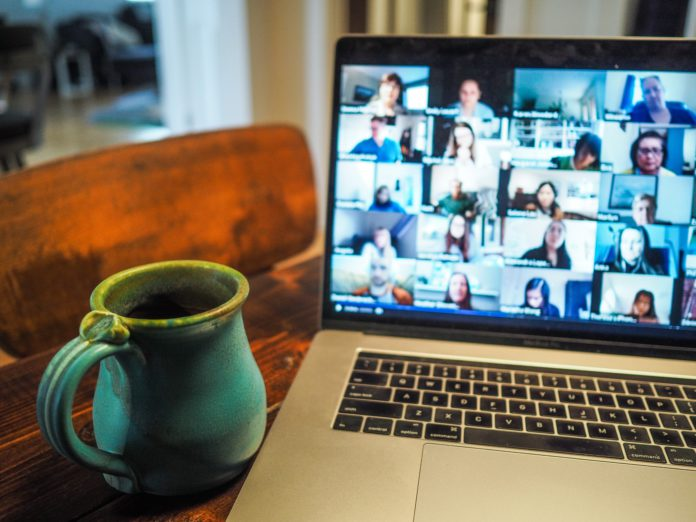 A full coffee mug sits near a laptop on a video conference call.