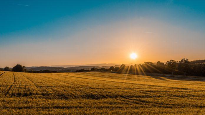 The sun sets over sprawling farmlands.