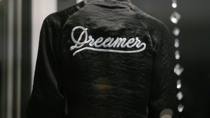 Someone faces away wearing a Dreamers jacket.