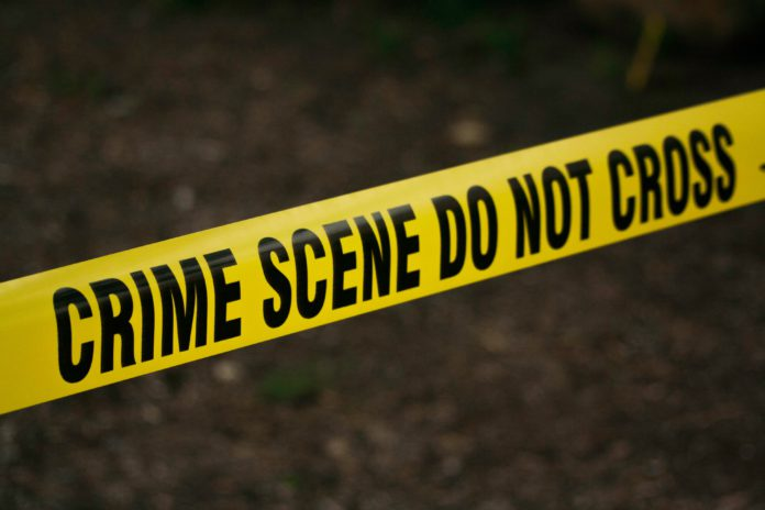 Bright yellow crime scene tape is in focus with a dark, murky background