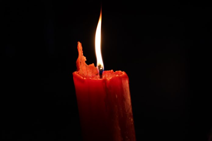 The flame of a red candle flickers in the darkness