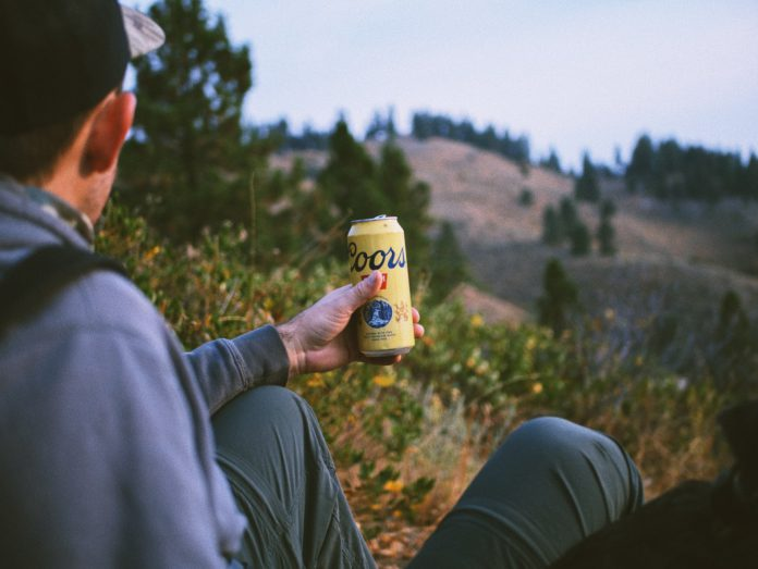 A hiker looks down at a Coors beer can.