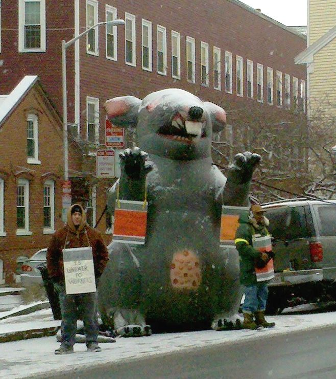 Scabby the Rat, an inflatable rat used by union protestors, sits in the snow outside of a building nearby a picketer.