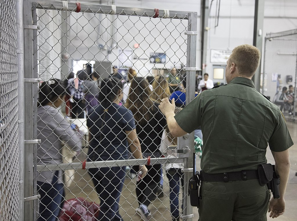 An immigration detention center officer holds a gate open for detainees