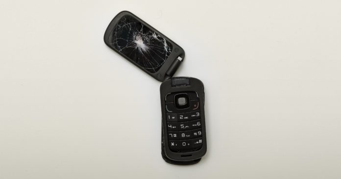 A flip-phone sits ripped in half with a cracked screen.